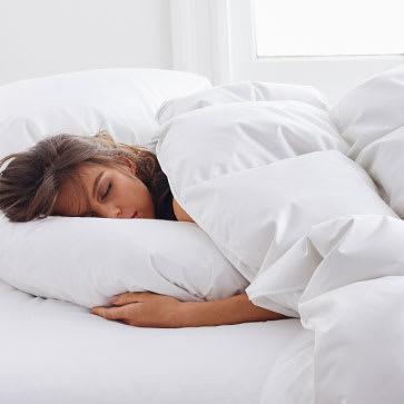 Woman asleep with LaCrosse™ Comforter