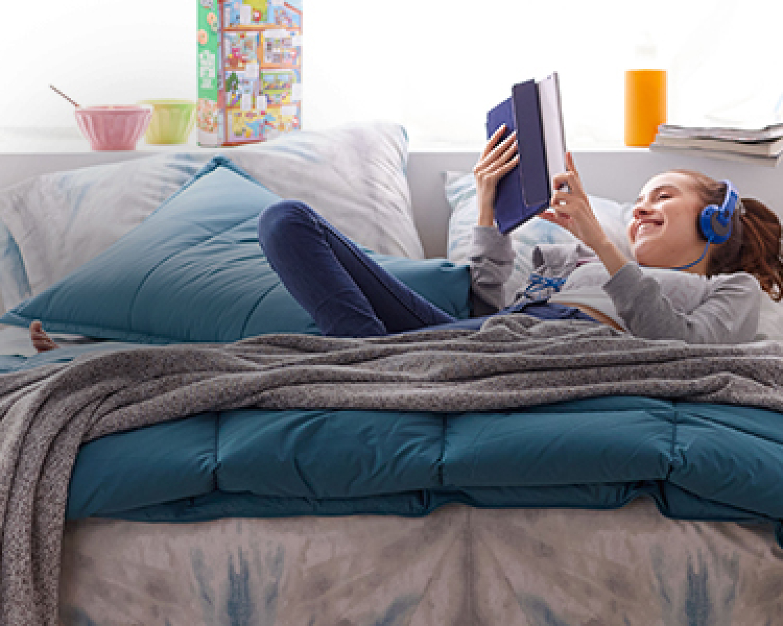 College student with headphones laying on comforter reading her tablet