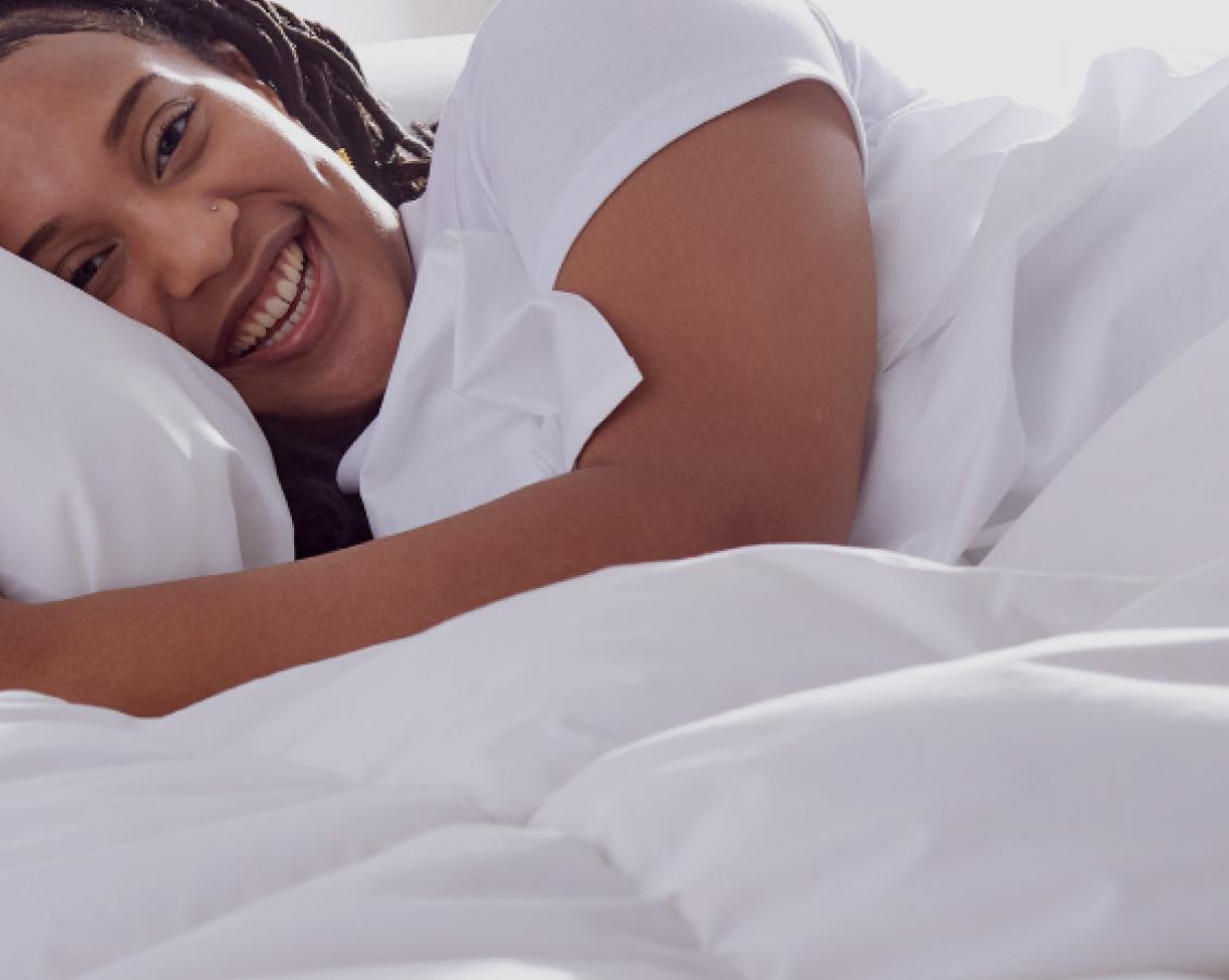 Girl laying down on comforter smiling